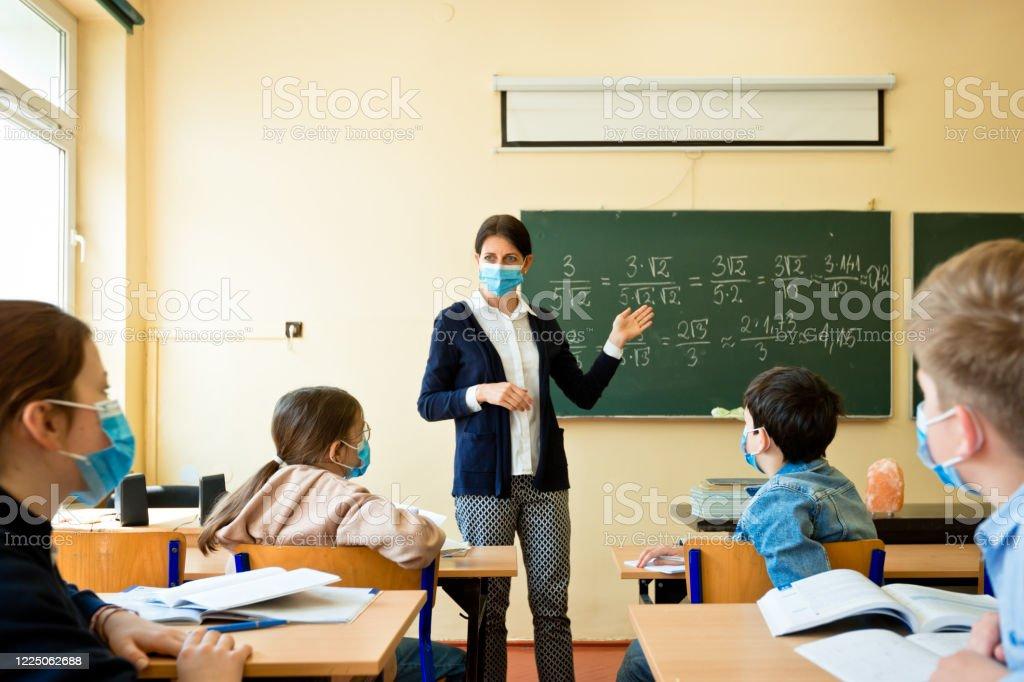 Covid-19. Un insegnante insegna matematica - Foto stock royalty-free di 40-44 anni