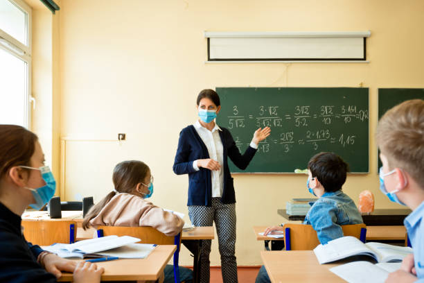 Covid-19. A teacher teaches mathematics A teacher wearing a N95 Face masks teaches mathematics at an High School school building stock pictures, royalty-free photos & images