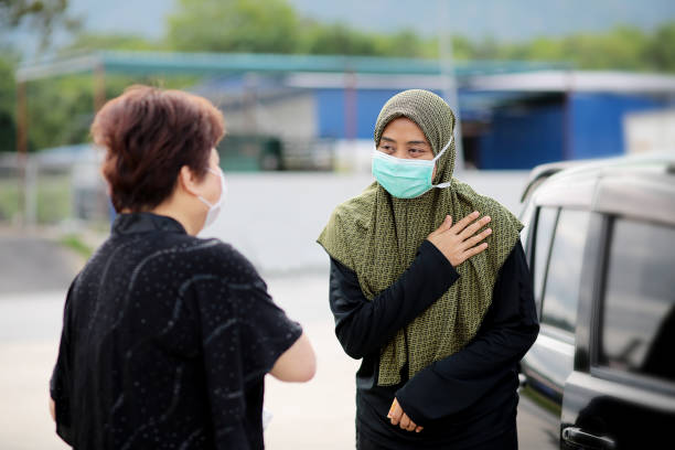 Covid-19 Alternative Handshakes A Muslim female adult placed her right palm on left chest as an alternative handshake in Malaysia. avoidance stock pictures, royalty-free photos & images