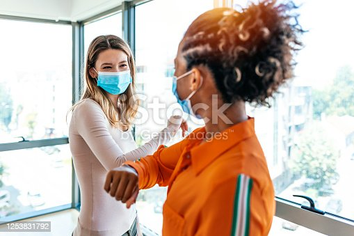Two colleagues in medical masks avoiding  handshake when meeting in the office, greeting with bumping elbows during corona virus COVID-19 epidemic in office, Social distancing concept