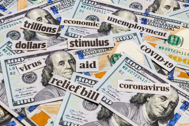 Covid-19 coronavirus newspaper headlines and 100 dollar bills. Stimulus aid relief bill, unemployment and recession concept stock photo