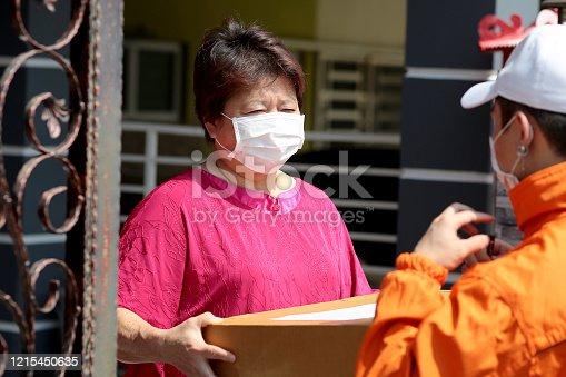 A young man wearing hat and surgical mask delivering parcel to a female adult at residence address due to lockdown in Malaysia.Most of the employees was instructed to work from home and avoid from going out unless in very necessary situation like visiting hospital or buying groceries and necessities.
