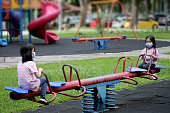 Two young girls are sitting at seesaw at playground during partial lockdown in Malaysia.
