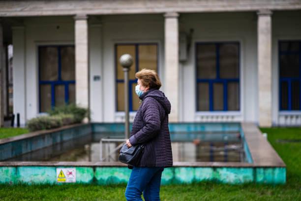 Covid-19 Grippevirus Verbreitung in Europa. Menschen, die medizinische Maske gegen Coronavirus, Influenzaviren und Krankheiten tragen. Gesundheitskonzept. Frau trägt chirurgische Maske auf gesicht in öffentlichen Räumen in Bukarest, Rumänien, 2020 – Foto