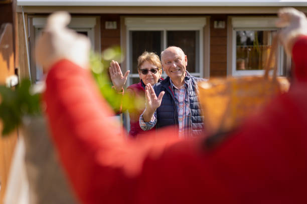 covid-19 food delivery, happy senior couple waving in front of their house - epidemiologia foto e immagini stock
