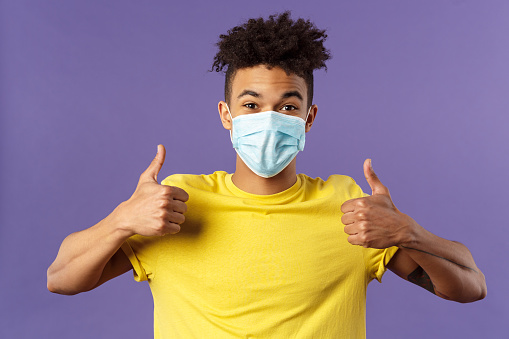 Covid19, healtcare and medicine concept. Enthusiastic happy spanish guy in facial mask, show thumbs-up and smiling with eyes, excited, support social-distancing, prepared for going grocery shopping