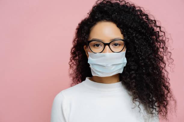 covid-19, infektiöses virus. nahaufnahme von jungen frau mit lockigen buschigen haaren, trägt transparente brille und medizinische einwegmaske, kümmert sich um ihre gesundheit, schützt in gefährlicher situation - brille stock-fotos und bilder