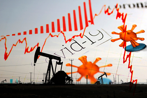 Silhouette of a pump jack with Corona / Covid-19 newspaper headlines and red declining financial market trend