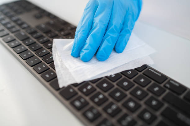 Covid-19 sanitizing office space wiping corona virus cleaning and disinfection of your workspace. Disinfecting wipes to wipe surface of desk, keyboard, mouse at office. Stop the spread of coronavirus stock photo