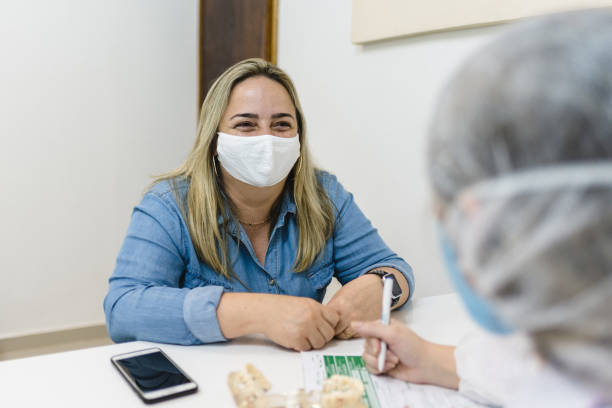 Covid19: Smiling woman during medical consultation New normal outpatient stock pictures, royalty-free photos & images