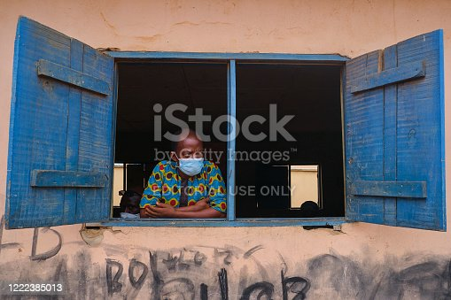 A man looks out the window at a venue for the Lagos State Environmental Protection Agency (LASEPA) and the Lagos State Safety Commission Social Distancing Advocacy program at Ikorodu, Lagos.
