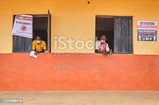 Two men look out the window at a venue for the Lagos State Environmental Protection Agency (LASEPA) and the Lagos State Safety Commission Social Distancing Advocacy program at Ikorodu, Lagos.