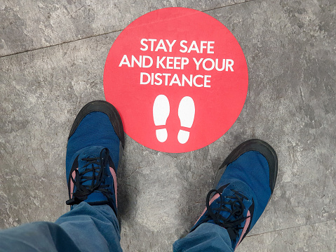 A sign on the floor of a shop, advising customers regarding social distancing guidelines.