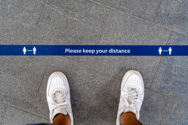 Covid-19 social distancing notice banner on ground stock photo