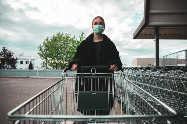 Covid-19 Supermarket Shopping Young Woman with Surgical Mask stock photo