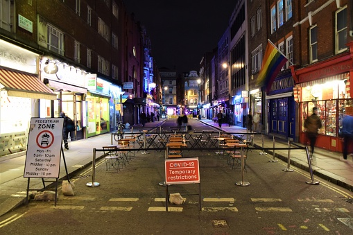 Covid-19 Temporary Restrictions sign and closed restaurants in Soho, London, night-time