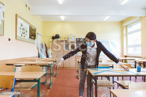 The teacher measuring and marking places in the classroom that are to be empty after students return to school after the coronovirus pandemic. Covid-19