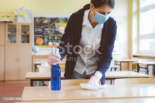 The teacher wipes down tables in the classroom before students return to school after the coronovirus pandemic. Covid-19