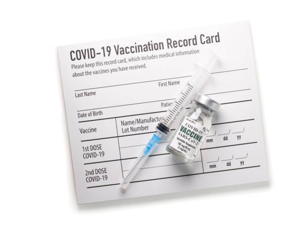 Covid-19 vaccination record card with syringe and vial stock photo