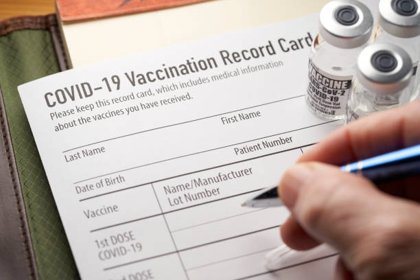 Covid-19 vaccination record card with vials and syringe. stock photo