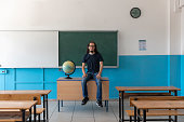 istock Covid19 virus pandemic. Teacher who sit on the desk wait in the classrom for education. 1271883829