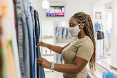 istock Covid-19: Woman customer choosing clothes at the mall store 1250722523