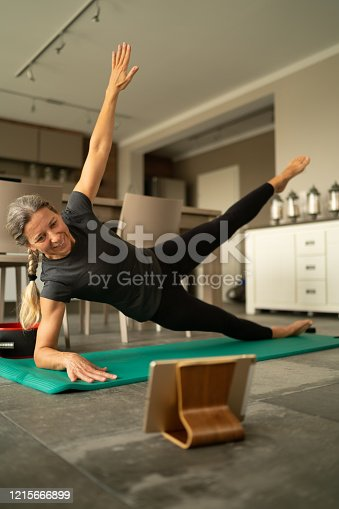 happy smiling motivated mature adult woman during online fitness workout at home in times of coronavirus curfew to stay fit and healthy