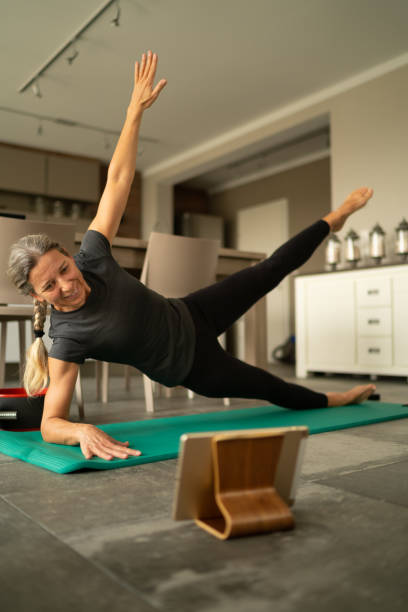 Covid-19 woman during online fitness training at home stock photo