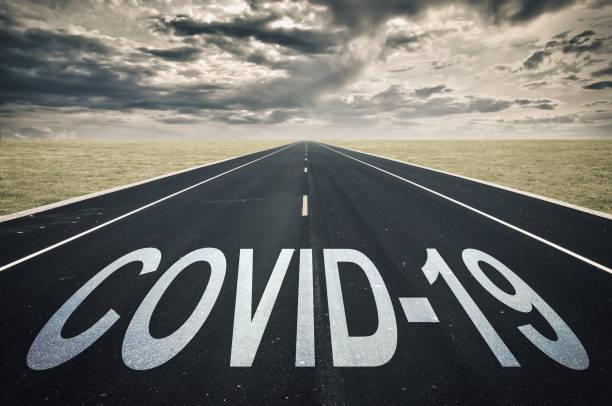 Covid-19 geschrieben auf einer Straße, dunkle Wolken, Coronavirus-Epidemie-Krisenkonzept – Foto