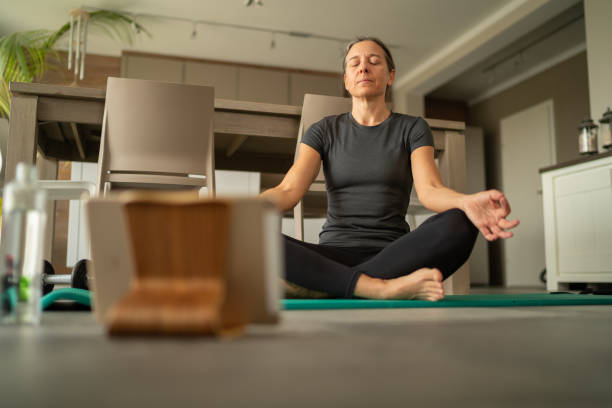 Covid-19 yoga breathing exercise at home low angle view mature adult woman doing yoga breathing relaxation exercises on gym mat at home, tablet blurred in foreground, coronavirus curfew, social distancing, pandemic quarantine flatten the curve stock pictures, royalty-free photos & images