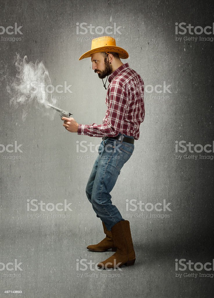 cow boy in a profile view using gun stock photo
