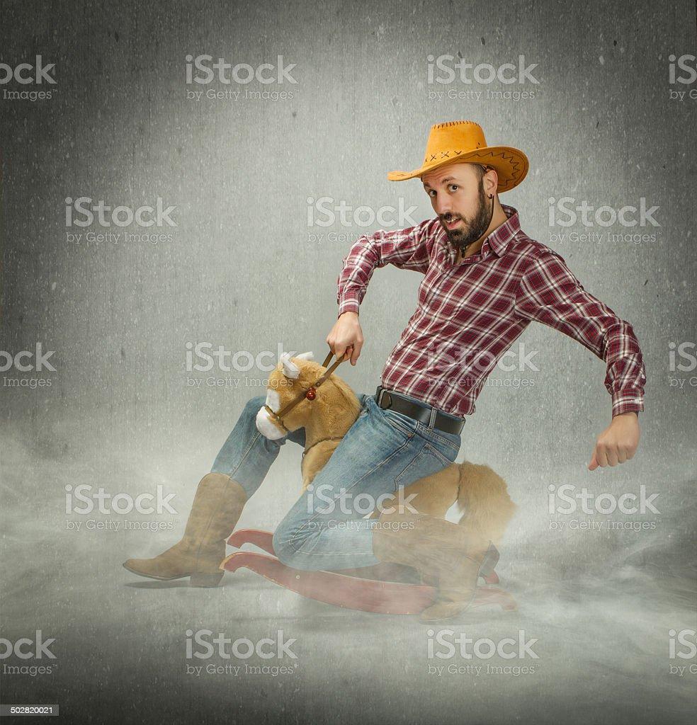 cow boy riding a fake horse stock photo