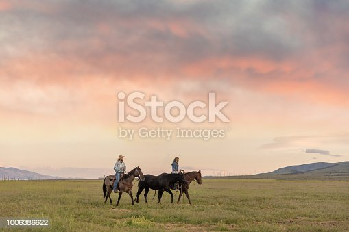 A cowboy and  his cowgirl ride off into the sunset.