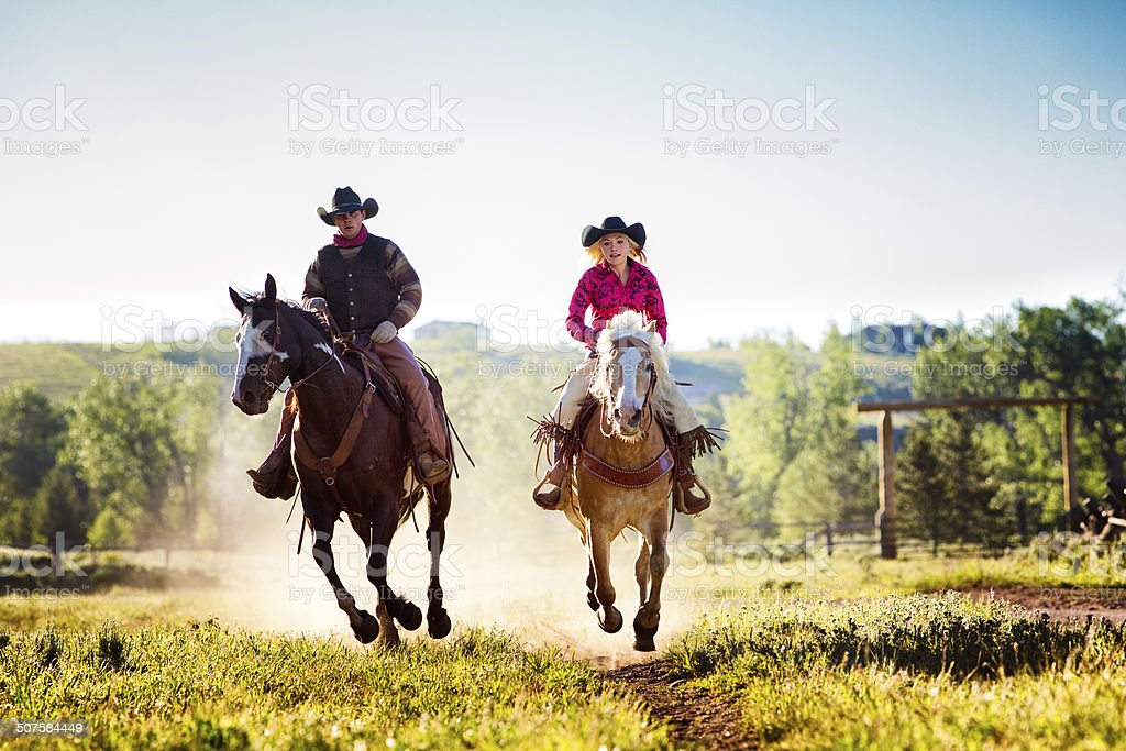 Cowboy and cowgirl riding on ranch stock photo