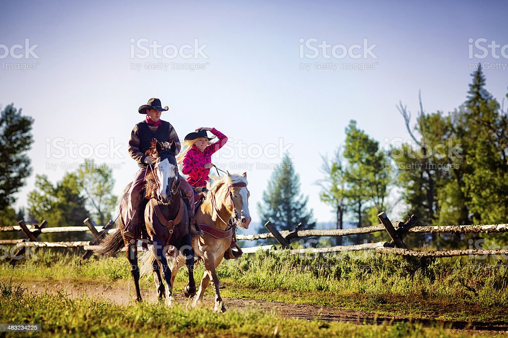 Cowboy and cowgirl riding stock photo