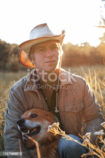 young man in cowboy style and his dog resting in the field toned image