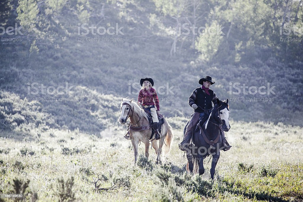 cowboy and partner ride out in backlit Montana morning royalty-free stock photo