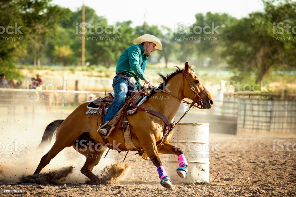 Cowboy Barrel Racing At The Rodeo - Fast and Furious To Beat Out The Competition stock photo
