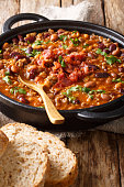 cowboy bean stew with ground beef, bacon in a spicy sauce close-up in a bowl on the table. vertical