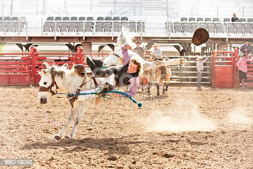 Young cowboy being thrown from a saddle bronc at a summer morning rodeo. Cowboy hat flying through the air.