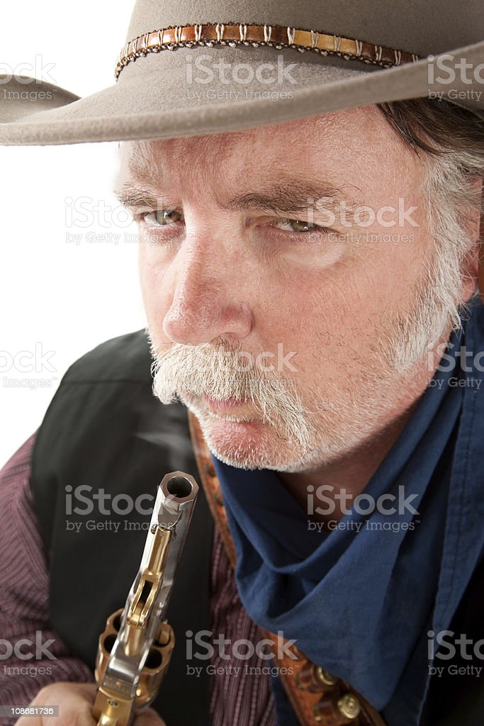 Cowboy blowing on the end of a hot pistol royalty-free stock photo