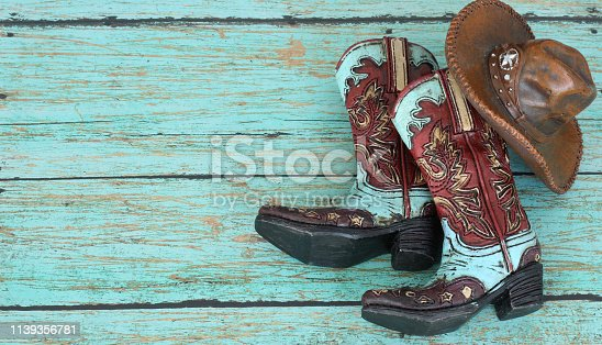 Colorful cowboy boots and brown hat with star laying flat on teal background