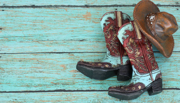 cowboy boots and hat laying on a teal painted wood background - rodeo stock pictures, royalty-free photos & images