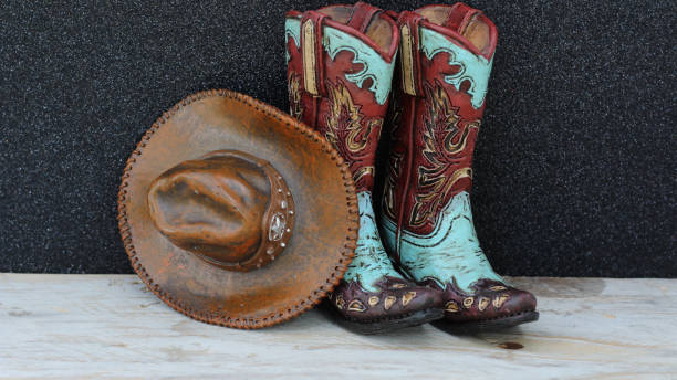 Cowboy boots and hat on a wood and black background stock photo