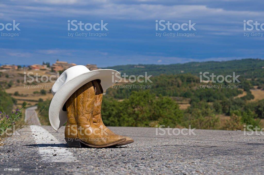 Botas de vaquero en una ruta - foto de stock
