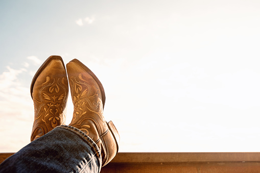cowboy resting legs with feet crossed - sky background - negative space - boots