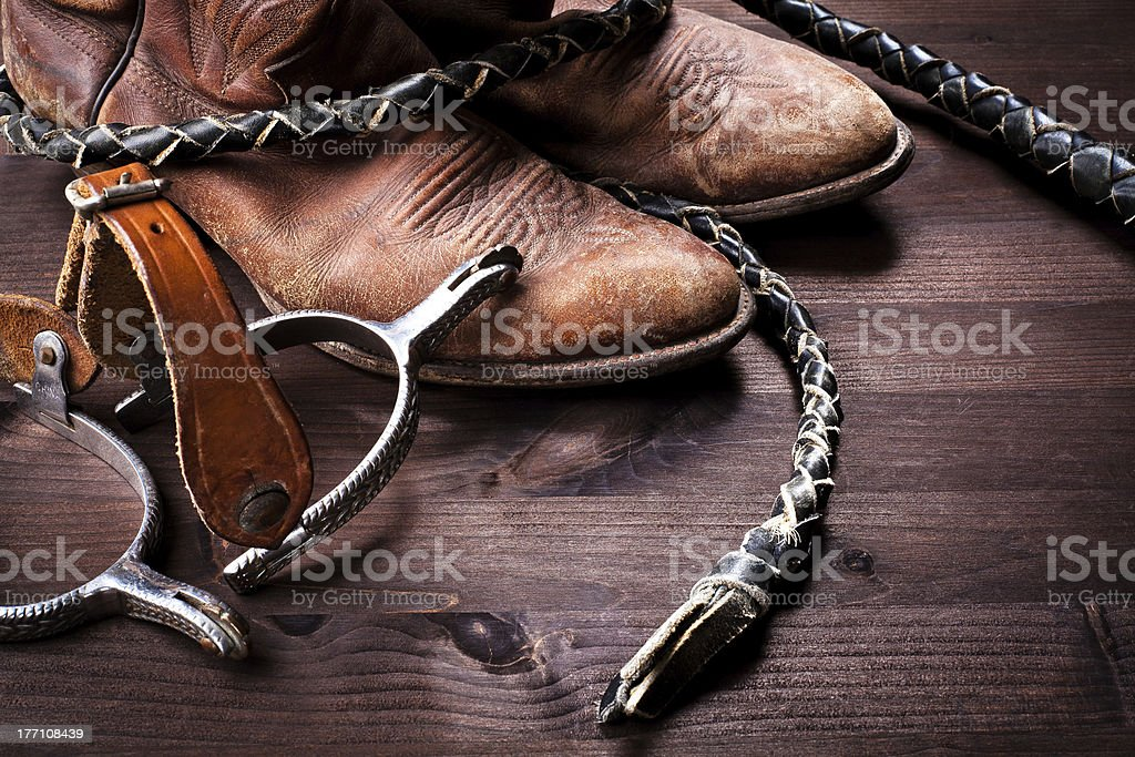 Cowboy boots,whip and spurs on wood stock photo