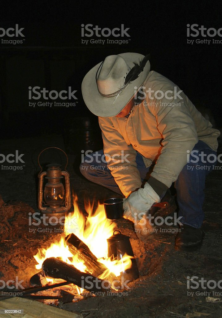 Cowboy By The Fire Before Dawn stock photo