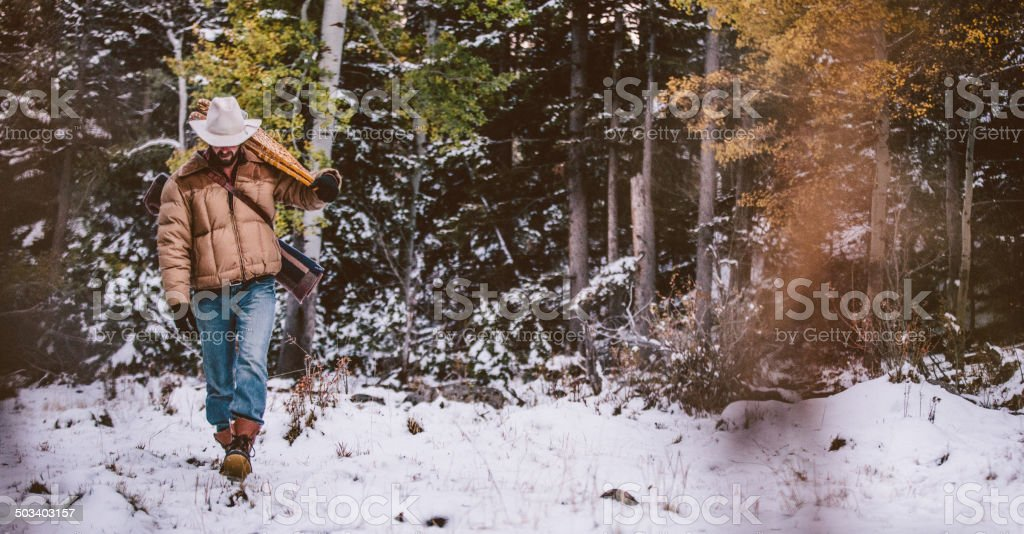 Cowboy carries snowshoes over shoulder while walking through snowy forest stock photo