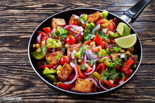 Delicious Cowboy Caviar cooked from colorful, fresh vegetables: green and red pepper, black beans, sweet corn, tomato, red onion, tofu cheese, garnished with parsley leaves, on a black skillet